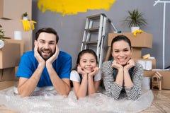 Gelukkige familie die op bellenomslag liggen die reparaties voor verkoop van plan zijn binnenshuis te doen stock foto