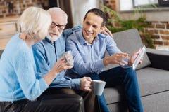 Gelukkige familie die op de laag babbelen terwijl het drinken van koffie stock foto's