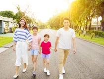 Gelukkige familie die op de straat lopen stock afbeelding