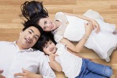 Gelukkige familie die op de vloer liggen Stock Fotografie