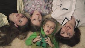 Gelukkige familie die op de vloer op pluizig tapijt, het glimlachen leggen De moeder en de jonge geitjes zijn gelukkig Grappig ki stock video