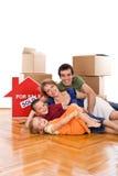 Gelukkige familie die op de vloer van hun nieuw huis legt Royalty-vrije Stock Afbeelding