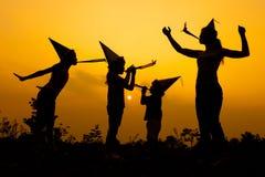 Gelukkige familie die op de weg in de zonsondergangtijd dansen avond Stock Afbeelding