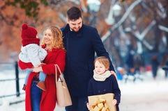 Gelukkige familie die op de winterstraat bij vakantie lopen stock foto's