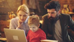 Gelukkige familie die op een film samen letten Kindjongen met laptop tussen mamma en vader die laptop met behulp van om op beeldv stock video