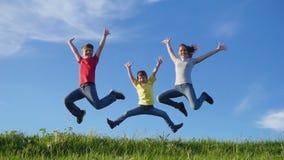 Gelukkige familie die op groene grasheuvel tegen blauwe hemel springen stock videobeelden