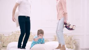 Gelukkige familie die op het bed springen en zacht speelgoed werpen Gelukkig familieconcept Vader, moeder en weinig jongenssprong stock footage