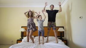Gelukkige familie die op het bed springen Gelukkig familieconcept Vader, moeder en weinig jongenssprong op het bed stock video