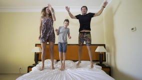 Gelukkige familie die op het bed springen Gelukkig familieconcept Vader, moeder en weinig jongenssprong op het bed stock videobeelden