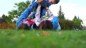 Gelukkige familie die op het gazon liggen Moeder en de vader die zijn zoon in zijn wapens over zijn hoofd de houden, het kind gli stock videobeelden