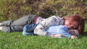 Gelukkige familie die op het gazon rusten De moeder met tederheid en liefde koestert haar kind, de zoonslach Gelukkige kinderjare stock footage