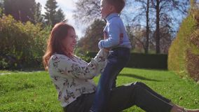 Gelukkige familie die op het gazon rusten De moeder met tederheid en liefdespelen met haar kind, de zoon lacht, heeft hij pret ge stock videobeelden