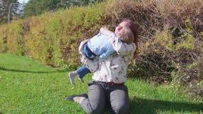 Gelukkige familie die op het gazon rusten De moeder met tederheid en liefdespelen met haar kind, de zoon lacht, heeft hij pret ge stock footage