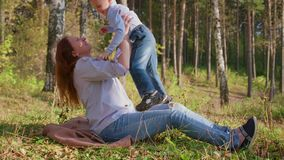 Gelukkige familie die op het gazon rusten De moeder met tederheid en liefdespelen met haar kind, de zoon lacht, heeft hij pret ge stock video