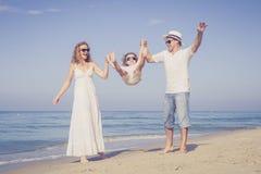Gelukkige familie die op het strand in de dagtijd lopen Stock Afbeeldingen