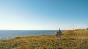 Gelukkige familie die op strand met dochter op handen lopen stock video