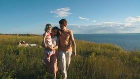 Gelukkige familie die op strand met dochter op handen lopen stock footage
