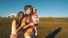 Gelukkige familie die op strand met dochter op handen lopen stock videobeelden