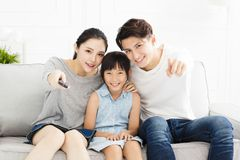 Gelukkige familie die op TV in woonkamer letten stock afbeelding