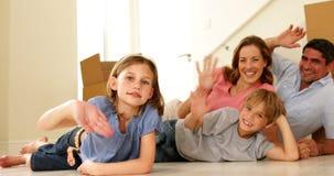 Gelukkige familie die op vloer in hun nieuw huis liggen die bij camera golven stock video