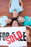Gelukkige familie die op vloer na het kopen van een huis ligt Stock Afbeelding