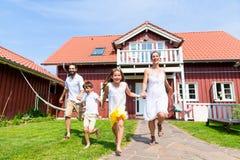 Gelukkige familie die op weide voor huis lopen royalty-vrije stock afbeeldingen