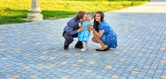 Gelukkige familie die in park loopt royalty-vrije stock afbeeldingen