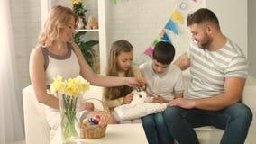 Gelukkige familie die Pasen vieren en een konijn strijken stock videobeelden