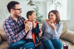 Gelukkige familie die pizza eten terwijl thuis het zitten op bank royalty-vrije stock foto