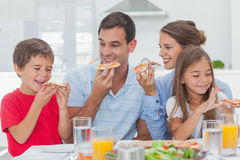 Gelukkige familie die pizzaplakken eten Stock Foto