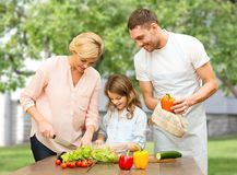 Gelukkige familie die plantaardige salade voor diner koken Royalty-vrije Stock Foto's