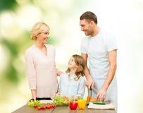 Gelukkige familie die plantaardige salade voor diner koken Stock Afbeeldingen