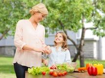 Gelukkige familie die plantaardige salade voor diner koken Stock Foto