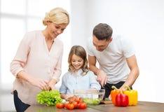 Gelukkige familie die plantaardige salade voor diner koken Stock Foto's