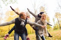 Gelukkige familie die pret in de herfstpark heeft Royalty-vrije Stock Afbeelding