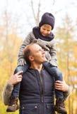 Gelukkige familie die pret in de herfstpark heeft Stock Afbeelding