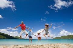 Gelukkige familie die pret heeft bij tropisch strand. Royalty-vrije Stock Afbeeldingen
