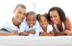 Gelukkige familie die pret heeft die op bed ligt Stock Afbeelding