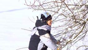 Gelukkige familie die pret het spelen in de sneeuw hebben Mamma en haar twee kinderen Zij schudden de sneeuw van de boom en de la stock video