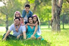 Gelukkige familie die pret in openlucht in de lentepark heeft Stock Foto