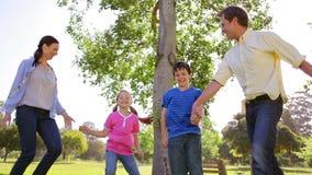 Gelukkige familie die samen op het gras dansen stock video