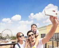 Gelukkige familie die selfie in het park nemen stock foto's