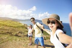 Gelukkige familie die selfie op de kust nemen stock afbeeldingen