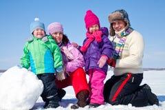 Gelukkige familie die sneeuwman maakt Royalty-vrije Stock Afbeelding