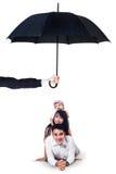 Gelukkige familie die in studio onder paraplu liggen Royalty-vrije Stock Foto's