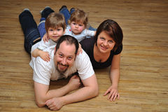 Gelukkige familie die thuis op houten vloer glimlachen royalty-vrije stock foto