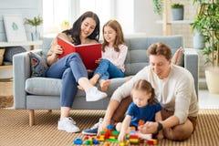 Gelukkige familie die thuis speelt stock afbeeldingen