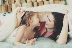 Gelukkige familie die thuis speelt Moeder en peuterdochter die en pret in bed ontspannen hebben royalty-vrije stock afbeelding