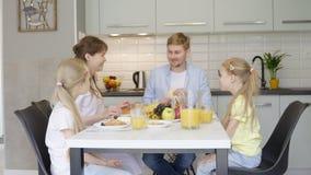 Gelukkige familie die tijdens ontbijt spreken stock video