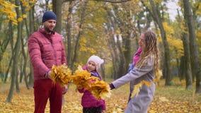 Gelukkige familie die van mooi dalingsseizoen in park genieten stock video